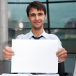 Attractive man in business suit with blank sign sitting at his o — Stock Photo