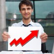 Attractive man in business suit with sign of up graph sitting at — Stock Photo #8773198