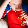 Young man holding soccer ball and beer and watching tv translati - Lizenzfreies Foto