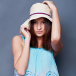 Confident woman with arms near her head holding hat against a bl — Stock Photo #8773234
