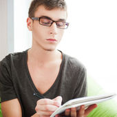 Young adult man writing in his copybook while sitting on a large — Stock Photo