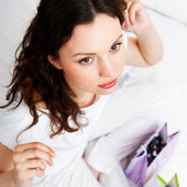 Portrait of young beautiful awake woman with gifts on bed at bed — Stock Photo