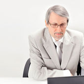 Portrait of an older businessman with a computer and a cup. — Stock Photo