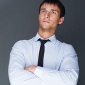 Primo piano di un giovane uomo d'affari sorridente in piedi con fiducia aga — Foto Stock
