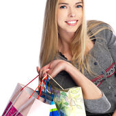 Side view of woman holding shopping bags against white backgroun — Stockfoto
