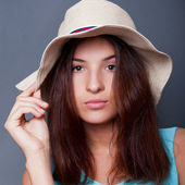 Confident woman with arms near her head holding hat against a bl — Stock Photo