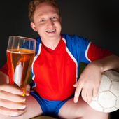 Young man holding soccer ball and beer and watching tv translati — Stock Photo