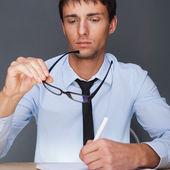 Portret biznes dorosły człowiek siedzi w biurze i znak — Zdjęcie stockowe