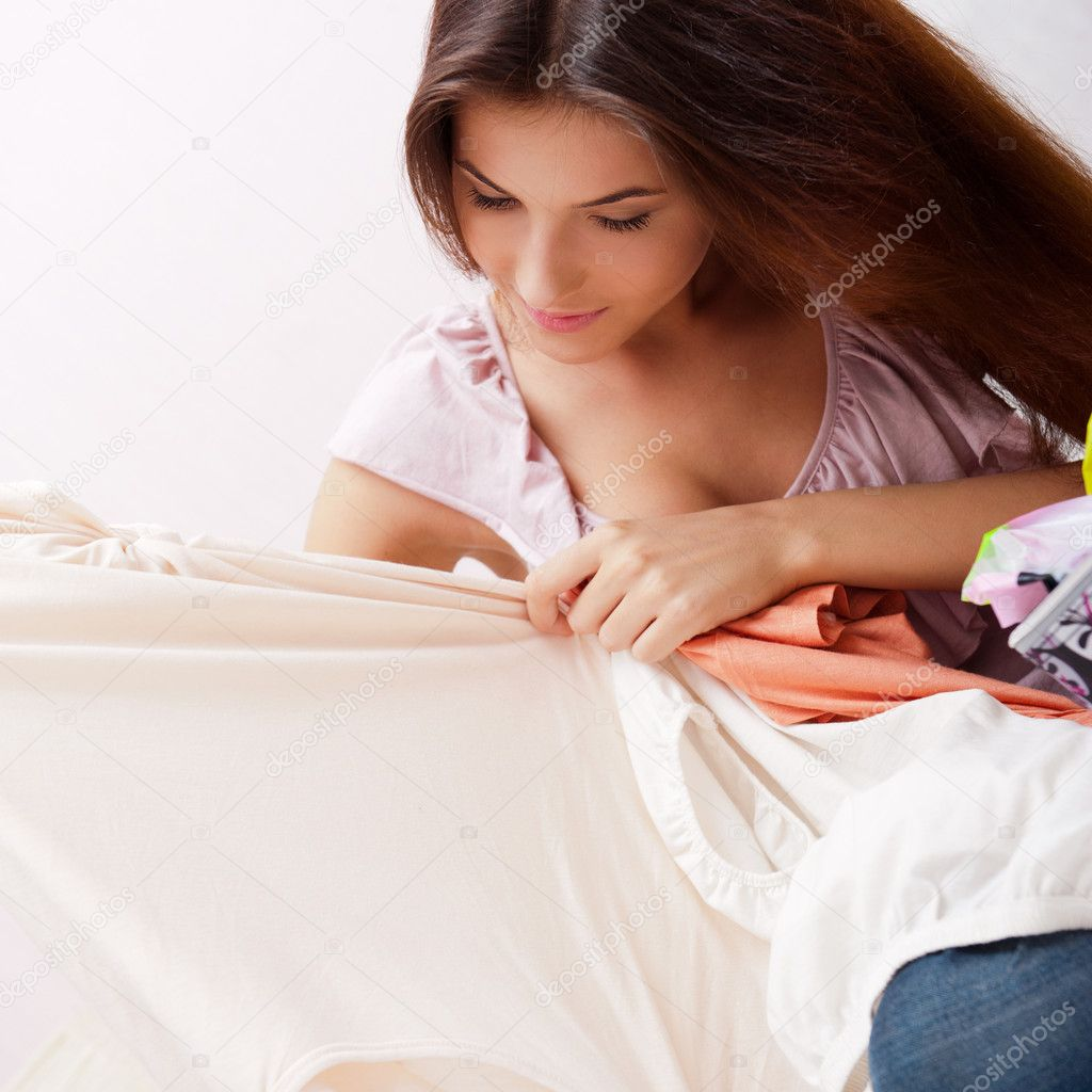 Beautiful young slim woman on the bed indoors unpacking clothes from suitcase — Stock Photo #8773173