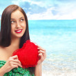 Cute young woman holds a heart symbol outdoors at beautiful view - Stock Photo