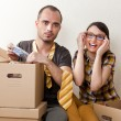 Young Couple with boxes in the new apartment sitting on floor and planning  — Stock Photo