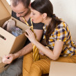 Young Couple with boxes in the new apartment sitting on floor and planning - Foto de Stock