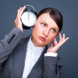Business woman listening to alarm clock against grey background — Stock Photo