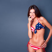 20-25 years old beautiful woman in swimsuit with american flag against grey — Stockfoto
