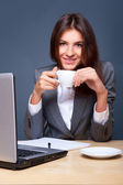 A pretty concentrated woman working with her laptop and papers. Sitting at — Stock Photo