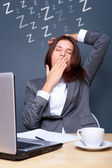 Bored businesspeople: woman sitting at desk with closed eyes. Young caucasi — Stock Photo