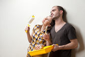 Happy smiling couple painting interior wall of home and having fun — Stock Photo