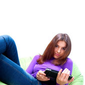 Young adult woman using her tablet computer while sitting on a large beanba — Stock Photo