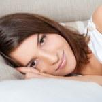 Beautiful Smiling Woman resting on sofa at home and looking at camera — Stock Photo