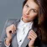 retrato de uma mulher de negócios jovem linda de pé contra backgrou cinza — Foto Stock
