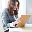 Beautiful business woman looking at papers she holding in her arms while wo — Stock Photo #9105918