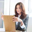 A portrait of a young business woman in an office with documents in her arm — Stock Photo #9105938