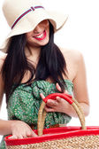 Portrait of a beautiful young woman wearing summer hat and holding handbag — Stock Photo