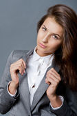 Portrait of a beautiful young business woman standing against grey backgrou — Stock Photo