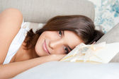 Donna felice leggendo un biglietto di auguri, seduto sul divano di casa — Foto Stock