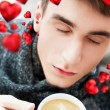 Portrait of a young man drinking coffee while sitting on armchair at home and dreaming about his couple. Red hearts are flying around his head. Valentine concept — Stock Photo