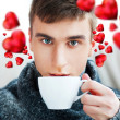 Portrait of a young man drinking coffee while sitting on armchair at home and dreaming about his couple. Red hearts are flying around his head. Valentine concept — Stock Photo #9246744