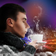 Close-up portrait of young man enjoying hot beverage magical poster — Stock Photo