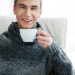 Portrait of a smiling young man drinking coffee while sitting on armchair at home — Stock Photo