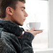 Portrait of a young man drinking coffee with his eyes closed — Stock Photo