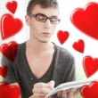 Portrait of attractive young man with hearts flying around him sitting at his home and writing using pen and copybook — Stock Photo