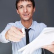 Handsome businessman giving a pen to sign documents — Stock Photo