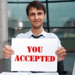 Attractive min business suit with acceptance sign sitting at his office and smiling to camera — Stock Photo #9247475