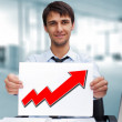 Attractive man in business suit with sign of up graph sitting at his office and smiling to camera — Stock Photo