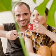 Stock Photo: Attractive young adult couple sitting close on hardwood floor in home smiling, drinking beverage and laughing. Monstera plant on foreground in blur