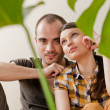 Attractive young adult couple sitting close on hardwood floor in home smiling and laughing. Monstera plant on foreground in blur — Stock Photo