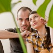 Attractive young adult couple sitting close on hardwood floor in home smiling and laughing. Monstera plant on foreground in blur — Stock Photo #9247952