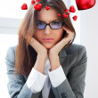 Portrait of a bored serious businesswoman working at her desk with paperwork and dreaming about love. Hearts are floating around her head — Stock Photo
