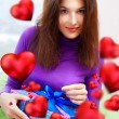 Delighted woman opening a gift sitting on the bean bag at home and beautiful red heart shapes are flying around. Valentine day concept poster — Stock Photo #9248375