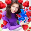 Delighted woman opening a gift sitting on the bean bag at home and beautiful red heart shapes are flying around. Valentine day concept poster — Stock Photo