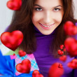 Stock Photo: Delighted woman opening a gift sitting on the bean bag at home and beautiful red heart shapes are flying around. Valentine day concept poster