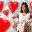 Portrait of happy young woman sitting on sofa at her home. Romantic photo with red hearts — Stock Photo
