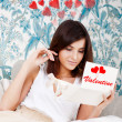 Portrait of young attractive happy woman, reading valentine card while sitting on comfortable sofa at living room at her home - Foto de Stock
