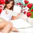 Stock Photo: Delighted woman reading a greeting card sitting on the sofa at home. Beautiful red hearts are floating around her
