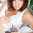 Smiling brunette woman eating some cake in the living room in her apartment — Stock Photo #9248448