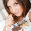 Smiling brunette woman eating some cake in the living room in her apartment — Stock Photo